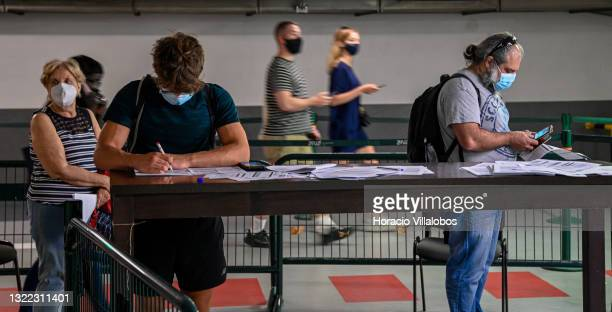 Mask-clad travellers fill out forms while queueing to be tested for COVID-19 at the Synlab post in Parking lot 1 of Humberto Delgado International...