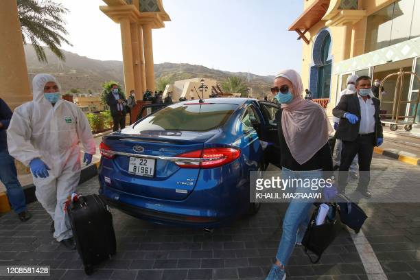 A maskclad woman leaves a Dead Sea resort where she has been quarantined for 14 days approximately 60 kilometres sout of the Jordanian capital Amman...