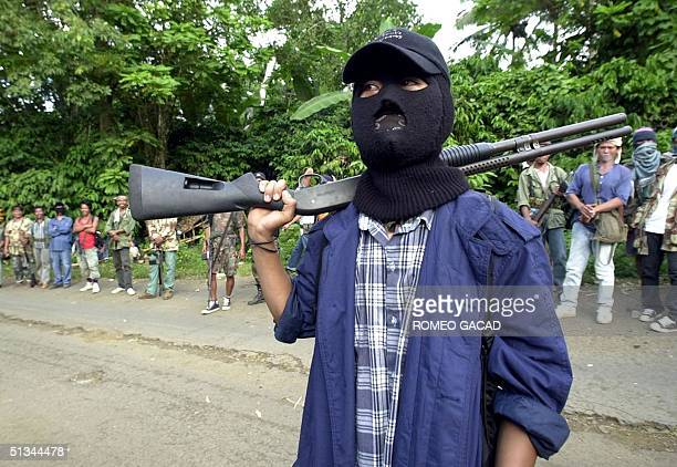 A masked Abu Sayyaf gunman and other rebels gather outside the mosque in Bandang in Jolo island 27 May 2000 while government negotiators meet Abu...