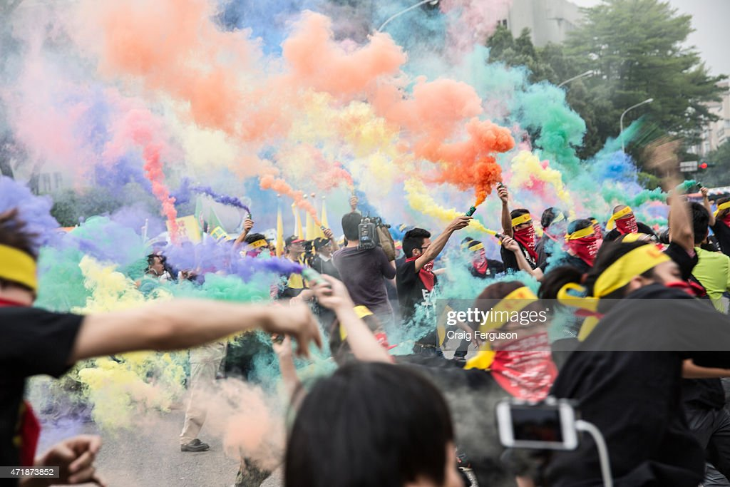 Masked activists throw colored smoke bombs toward the