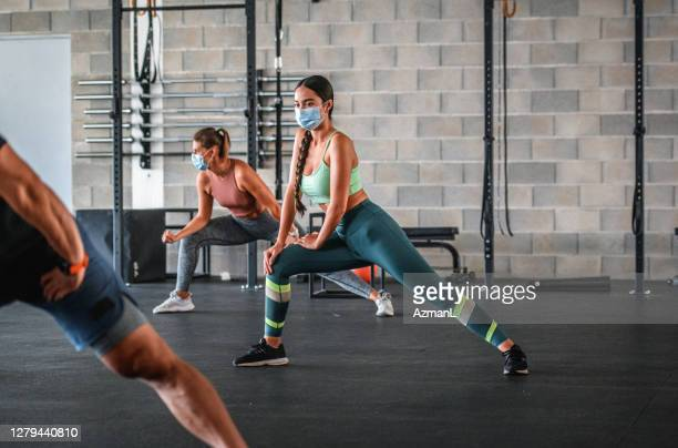 masked and distanced mixed race athlete stretching at gym - health club stock pictures, royalty-free photos & images