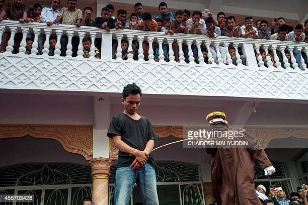 A masked and hooded official canes an Acehnese man for gambling in Banda Aceh on September 19 2014 Nine men were caned in public on September 19 in...