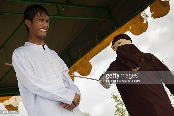 A masked and hooded official canes one of seven Acehmen for gambling in Jantho Aceh on December 5 2014 Seven men were caned in Aceh province on...