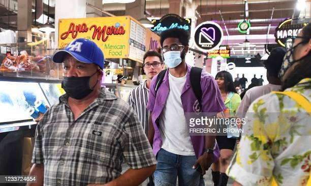 Masked and unmasked people make their way through Grand Central Market in Los Angeles, California on June 29, 2021 as World Health Organization urges...
