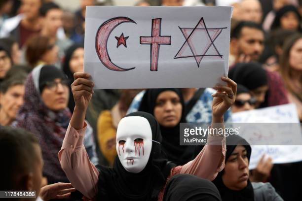 Masked and veiled woman holds a paper with the Star and Crescent, the Christain Cross and the Star of David. People gathered against islamophobia on...