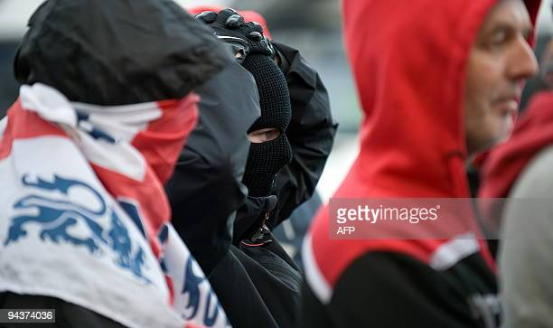 Masked anti-Islam demonstrators watch anti-fascist demonstrators outside the Harrow Central mosque in Harrow, west London, England on December 13,...