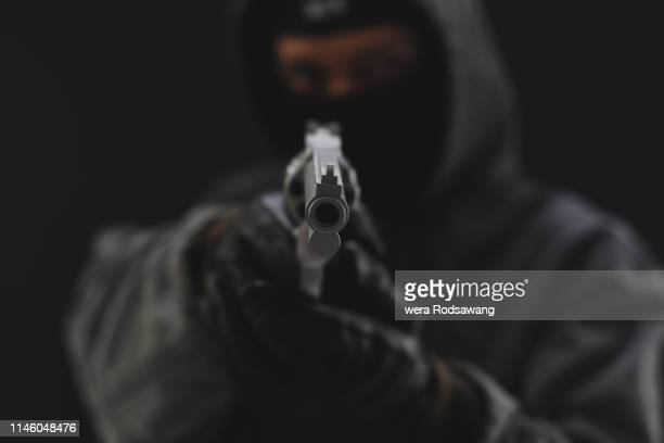 Masked Armed robbers pointing a handgun to robbery the money