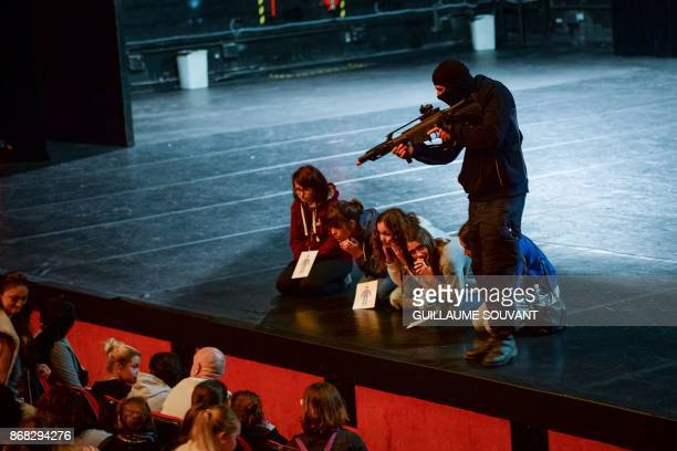 Masked assailant points a fire weapon on hostages during an exercise simulating a terrorist attack inside the theatre Espace Malraux in JouelesTours...