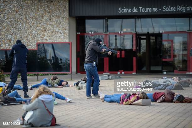Masked assailants point a fire weapon on hostages lying on the ground during an exercise simulating a terrorist attack inside the theatre Espace...