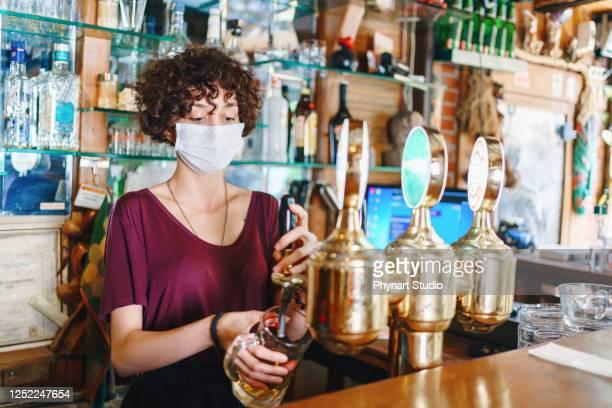 maskierte barkeeper füllung bier - corona beer stock-fotos und bilder