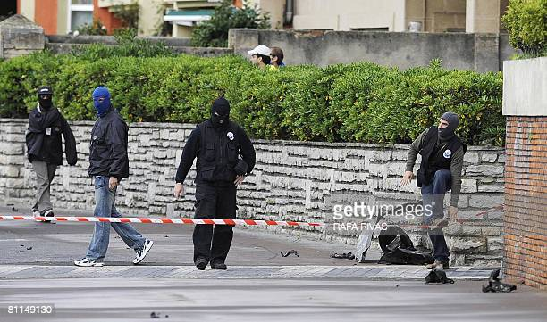 Masked Basque police officers look for evidence near the wreckage of a van that exploded early on May 19 2008 in front of the Maritime Club in the...