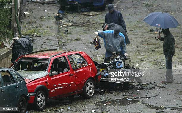 Masked Basque regional policemen examine the rests of a car bomb that exploded 18 January 2005 at Getxo in the Basque country with armed Basque...