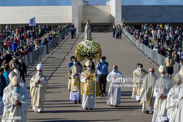 Masked bearers carrying the figure of Our Lady of Fátima are preceded by priests during the procession on the last day of the ceremonies in which...
