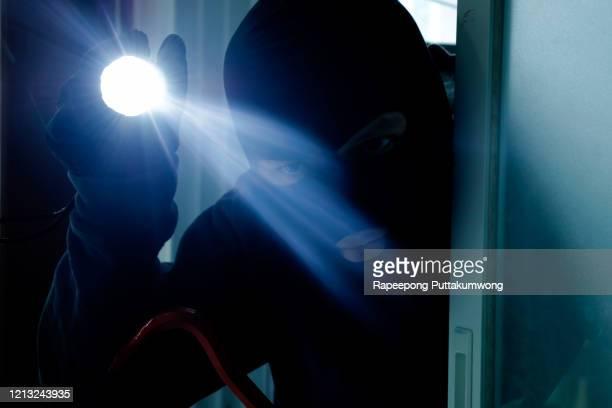 masked burglar holding flashlight while secretly entering into a house - burglary stock pictures, royalty-free photos & images
