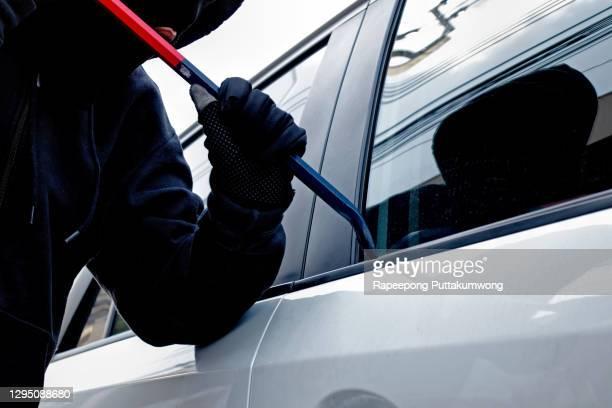masked burglar trying to get into a car - steel stockfoto's en -beelden