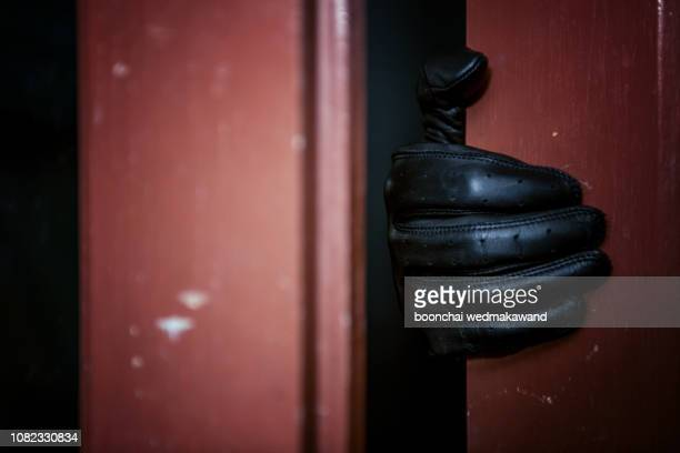 masked burglar with crowbar breaking and entering into a victim's home - image - burglar stock pictures, royalty-free photos & images