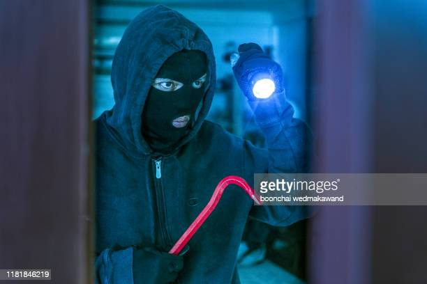 masked burglar with crowbar breaking and entering into a victim's home - burglar stock pictures, royalty-free photos & images