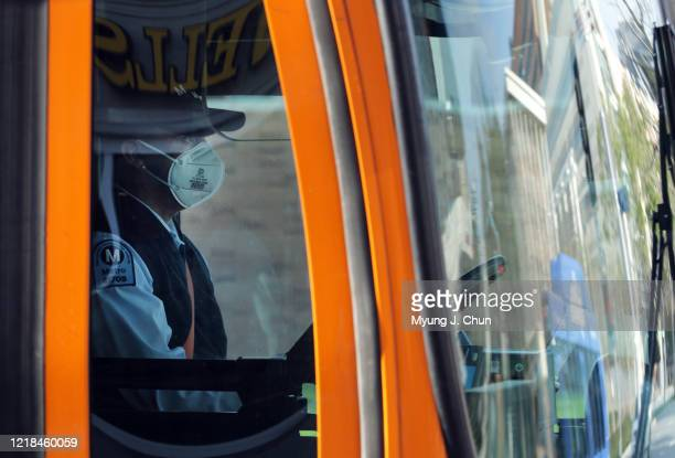 Masked bus driver waits at a light in Westwood Village. The coronavirus pandemic forced the closure of UCLA and neighboring businesses leading to...