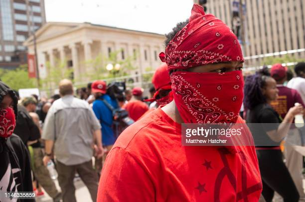 A masked counterprotester walks through a large crowd of other counter demonstrators during a protest against a rally held by the KKK affiliated...