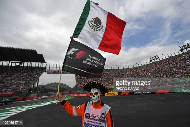 A masked course marshall waves a Mexican national flag prior to the start of the F1 Mexico Grand Prix at the Hermanos Rodriguez circuit in Mexico...