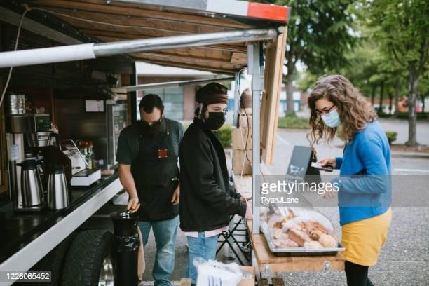 le client masqué commande le café et les collations au camion de nourriture - food truck photos et images de collection