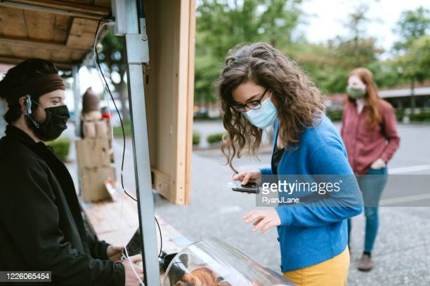 masked customer orders coffee and snacks at food truck - seattle stock pictures, royalty-free photos & images