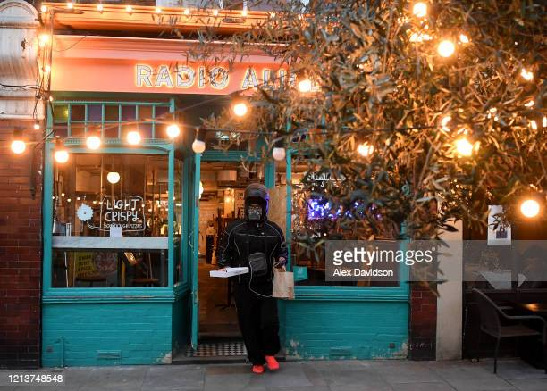 A masked delivery driver collects food from a restaurant in Clapham on March 20 2020 in London United Kingdom British Prime Minister Boris Johnson...