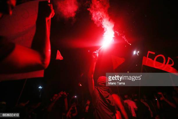 A masked demonstrator carries a flare during a protest against proposed federal government reforms on March 15 2017 in Rio de Janeiro Brazil...