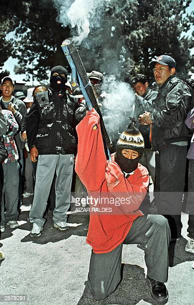A masked demonstrator fires a makeshift explosiveslauncher against the riot police 10 October 2003 during a massive protest along the streets of El...