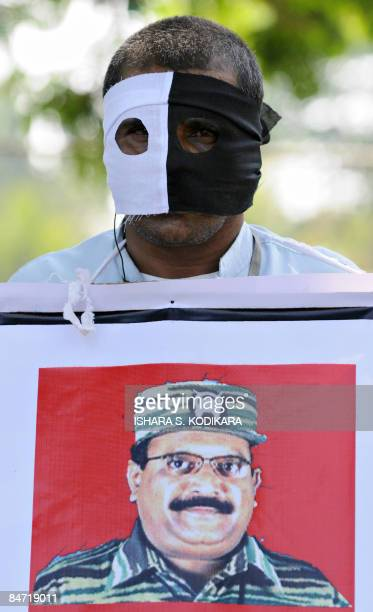 A masked demonstrator from Sri Lanka's Patriotic National Movement carries a placard bearing the portrait of Liberation Tigers of Tamil Eelam leader...