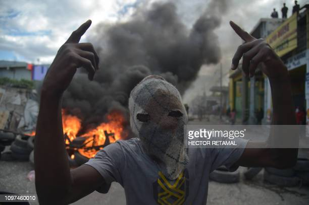 TOPSHOT A masked demonstrator gestures before burning tires on the fourth day of protests in PortauPrince on February 10 2019 Demonstrators are...
