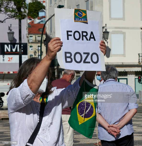 """Masked demonstrator holds a """"Fora Bolsonaro"""" sign as Brazilian residents gather in Praça Rossio to demand the ousting of Brazil's President, Jair..."""
