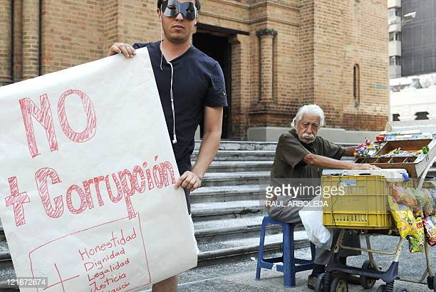 A masked demonstrator holds a placard that reads 'No More Corruption More Honesty Dignity Loyalty Justice and Education' during a march against...
