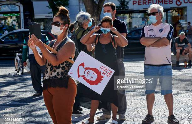 Masked demonstrator holds a placard with the face of Brazilian murdered PSOL Councilwoman Marielle Francoas Brazilian residents gather in Praça...
