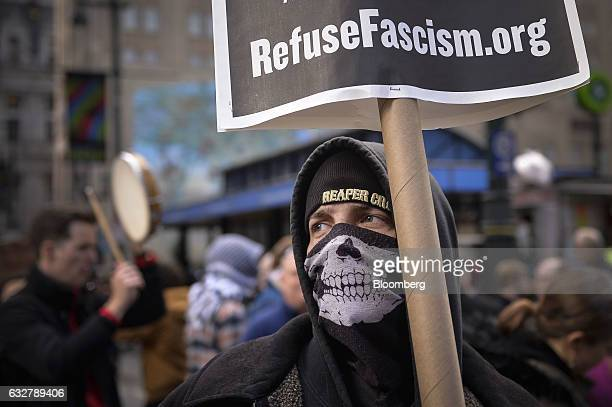 A masked demonstrator holds up a sign displaying the website for Refuse Fascism during a protest outside the Republican Party's annual policy retreat...