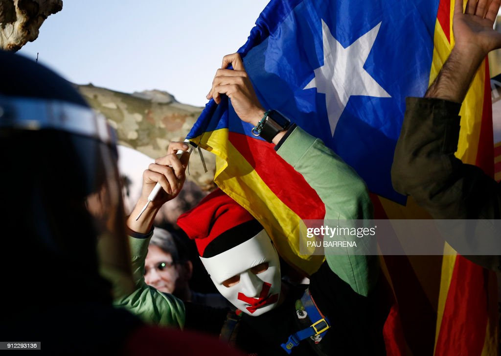 TOPSHOT - A masked demonstrator sporting the traditional Catalan hat 'Barretina' holds a 'Estelada' pro-independence flag during a demonstration outside the Catalan parliament on January 30, 2018 in Barcelona. The speaker of Catalonia's parliament Roger Torrent delayed a key debate in the regional assembly on ousted separatist leader Carles Puigdemont's bid to form a new government, but defended his right to return to power. / AFP PHOTO / Pau Barrena