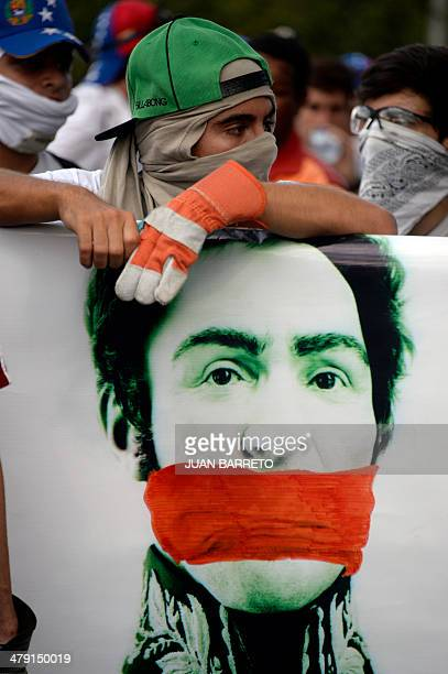 Masked demonstrators hold a banner with the portrait of Venezuelan liberator Simon Bolivar with a headscarf on his mouth during a protest against...