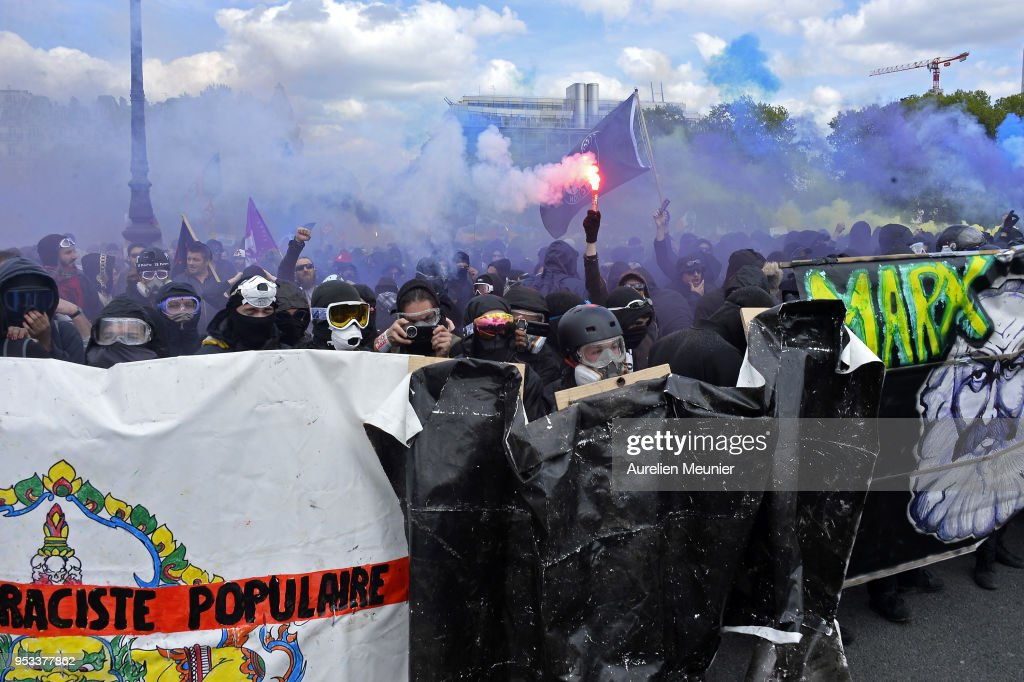 Masked demonstrators wave flares during the Labor Day demonstration on May 1, 2018 in Paris, France. According to the police around 1200 Black Bloc demonstrators took to the streets.