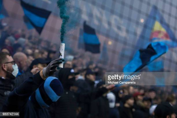 A masked Djurgarden supporter lights a smoke bomb during a semifinal match of the Swedish Cup between AIK and Djurgardens IF at Friends arena on...