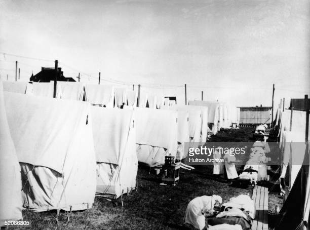 Masked doctors and nurses treat flu patients lying on cots and in outdoor tents at a hospital camp during the influenza epidemic of 1918.