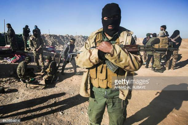 A masked fighter of the Hashed alShaabi paramilitaries poses for a picture carrying a Kalashnikov assault rifle by defensive positions near the...