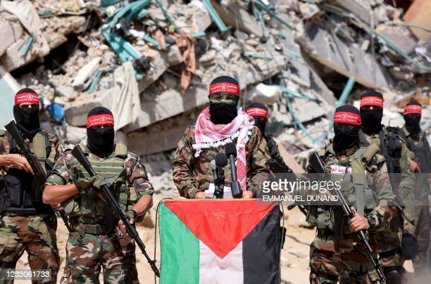 Masked fighters with the National Resistance Brigades , the military wing of the Democracy Front Liberation of Palestine , speak to members of the...