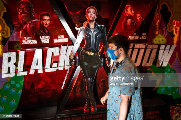 Masked film fan walks past a lobby display for Marvel Studios Black Widow, on opening weekend at the El Capitan Theatre, in the heart of Hollywood,...