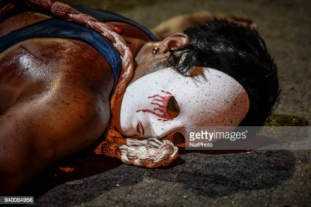 Masked flagellant lies on the ground during Good Friday Lenten rites in Navotas, Metro Manila, Philippines, March 30, 2018. Photo: Ezra...