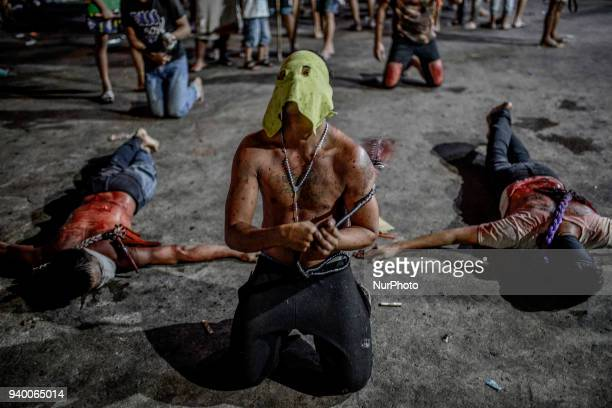 A masked flagellant whips himself during Good Friday Lenten rites in Navotas Metro Manila Philippines March 30 2018 Ezra Acayan/NurPhoto