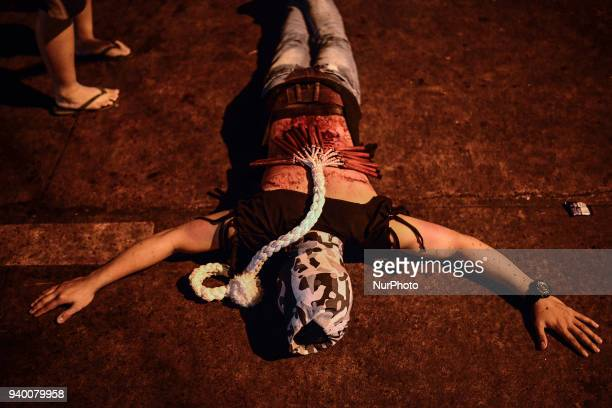 A masked flagellant with a bloodied back lies on the ground during Good Friday Lenten rites in Navotas Metro Manila Philippines March 30 2018 Ezra...