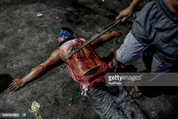A masked flagellant with a bloodied back lies on the ground while being kicked during Good Friday Lenten rites in Navotas Metro Manila Philippines...