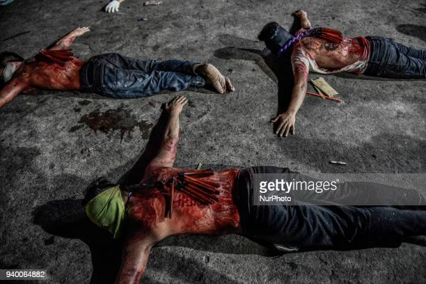 Masked flagellants with bloodied backs lie on the ground during Good Friday Lenten rites in Navotas Metro Manila Philippines March 30 2018 Ezra...