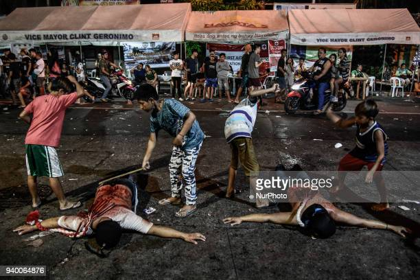 Masked flagellants with bloodied backs lie on the ground while being whipped by children during Good Friday Lenten rites in Navotas Metro Manila...