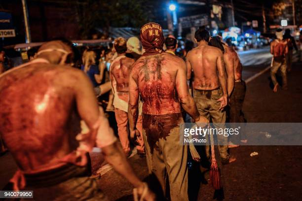 Masked flagellants with bloodied backs walk in a line during Good Friday Lenten rites in Navotas Metro Manila Philippines March 30 2018 Ezra...